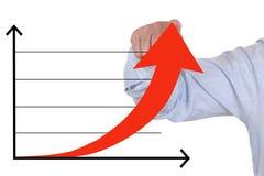 Hombre de negocios que muestra un levantamiento acertado encima de carta de crecimiento del negocio Imagen de archivo libre de regalías