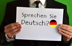 Hombre de negocios que muestra una hoja con el texto Sprechen Sie Deutsch Imagen de archivo