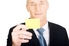 Hombre de negocios que muestra una tarjeta de presentación amarilla de la identidad Foto de archivo