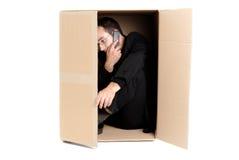 Hombre de negocios que oculta en un rectángulo del cartón Fotos de archivo