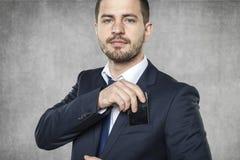 Hombre de negocios que oculta un teléfono Imagenes de archivo