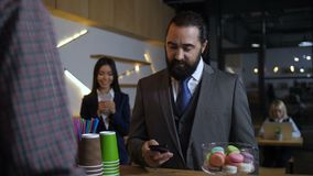 Hombre de negocios que ordena mientras que usando el teléfono móvil en el café metrajes