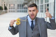 Hombre de negocios que oscila el collar de oro con la muestra de dólar fotos de archivo