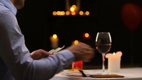 Hombre de negocios que paga el efectivo cena en el restaurante de lujo, dejando extremidad al camarero almacen de metraje de vídeo