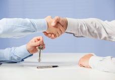 Hombre de negocios que pasa llaves a su socio y que sacude su mano Imagen de archivo