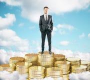 Hombre de negocios que permanece en la pila de monedas de oro en las nubes t s azul foto de archivo libre de regalías
