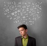 Hombre de negocios que piensa con los iconos sociales de la red sobre su cabeza Foto de archivo