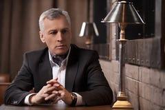 Hombre de negocios que piensa en las nuevas ideas para el negocio. MA pensativo Fotos de archivo libres de regalías