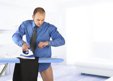 Hombre de negocios que plancha su pantalón imágenes de archivo libres de regalías