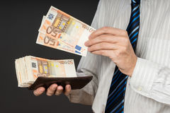 Hombre de negocios que pone billetes de banco en su cartera Pila de dinero de cincuenta euros El hombre de negocios está sostenie fotografía de archivo libre de regalías