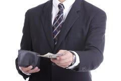 Hombre de negocios que pone el dinero del dólar para la paga algo Fotos de archivo libres de regalías