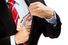 Hombre de negocios que pone el dinero en su bolsillo. Fotografía de archivo libre de regalías