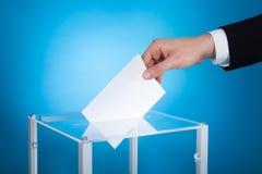 Hombre de negocios que pone el papel en caja de la elección Imagen de archivo libre de regalías