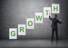 Hombre de negocios que pone encima de los carteles con las letras en el muro de cemento que forma y x27; growth& x27; palabra Fotografía de archivo libre de regalías