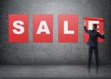 Hombre de negocios que pone encima de los carteles con las letras en el muro de cemento que forma y x27; sale& x27; palabra Fotos de archivo libres de regalías