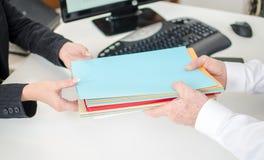 Hombre de negocios que pone ficheros en las manos de su secretaria Fotos de archivo libres de regalías