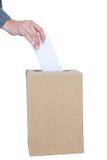 Hombre de negocios que pone la votación en caja del voto Imagen de archivo libre de regalías