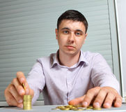 Hombre de negocios que pone las monedas en columnas Fotos de archivo libres de regalías
