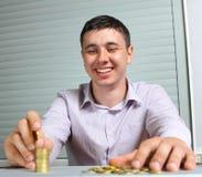 Hombre de negocios que pone las monedas en columnas Imágenes de archivo libres de regalías