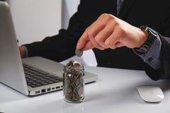 Hombre de negocios que pone monedas de oro en botella Foto de archivo libre de regalías