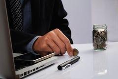 Hombre de negocios que pone monedas de oro en botella Imágenes de archivo libres de regalías