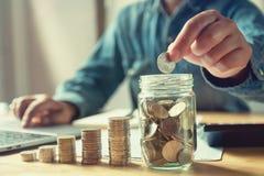 hombre de negocios que pone monedas en el vidrio del jarro dinero del ahorro del concepto imagen de archivo
