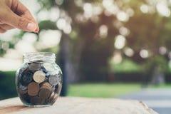Hombre de negocios que pone monedas en la botella, el concepto cada vez mayor del dinero y el éxito de la meta imagenes de archivo