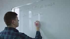Hombre de negocios que pone sus ideas en el tablero blanco durante una presentaci?n Distribuci?n de ideas y de estrategia del neg metrajes