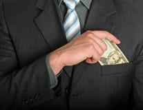 Hombre de negocios que pone una cuenta de dólar en su bolsillo Imágenes de archivo libres de regalías
