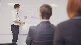 Hombre de negocios que presenta al equipo que toma notas en la sala de reunión Tiro estático metrajes