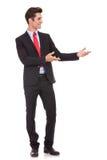 Hombre de negocios que presenta algo o que lo invita fotos de archivo