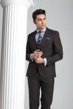 Hombre de negocios que presenta cerca de la columna blanca en fondo gris del estudio imagen de archivo libre de regalías