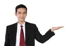 Hombre de negocios que presenta con la mano abierta, aislada en blanco Foto de archivo