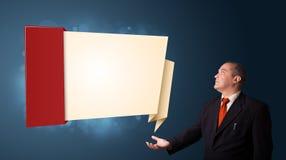 Hombre de negocios que presenta el espacio moderno de la copia del origami Imágenes de archivo libres de regalías