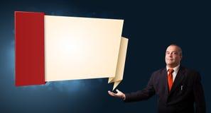 Hombre de negocios que presenta el espacio moderno de la copia del origami Imagen de archivo
