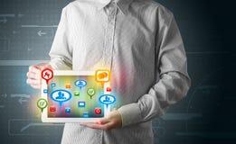 Hombre de negocios que presenta la tableta moderna con las muestras sociales coloridas Fotografía de archivo libre de regalías