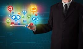 Hombre de negocios que presenta la tableta moderna con las muestras sociales coloridas Imagen de archivo