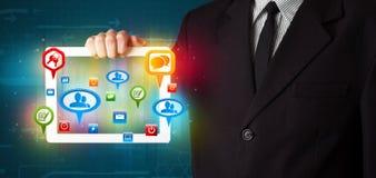 Hombre de negocios que presenta la tableta moderna con las muestras sociales coloridas Foto de archivo libre de regalías