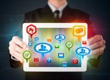 Hombre de negocios que presenta la tableta moderna con las muestras sociales coloridas Foto de archivo