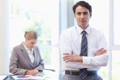 Hombre de negocios que presenta mientras que su colega está trabajando fotos de archivo