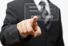 Hombre de negocios que presiona el botón de la autentificación en la exhibición del inicio de sesión imagen de archivo libre de regalías