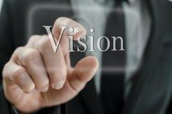 Hombre de negocios que presiona el botón de Vision en un interfaz de la pantalla táctil Fotos de archivo libres de regalías