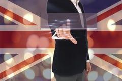 Hombre de negocios que presiona el botón en las pantallas virtuales, borrosas de fondo británico de las luces de la bandera y del Imagen de archivo