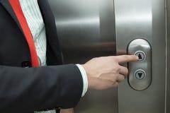 Hombre de negocios que presiona el elevador encima del botón Imagen de archivo