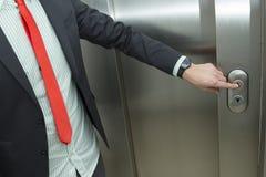 Hombre de negocios que presiona el elevador encima del botón Imagen de archivo libre de regalías