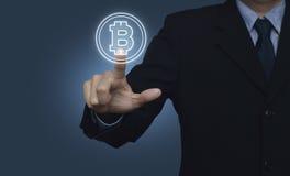 Hombre de negocios que presiona el icono del bitcoin en el fondo azul, eligiendo b Foto de archivo libre de regalías