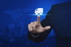 Hombre de negocios que presiona el icono del camión de reparto sobre mapa del mundo digital foto de archivo libre de regalías