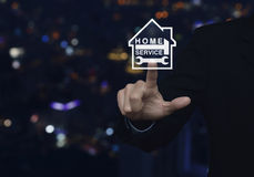 Hombre de negocios que presiona el martillo y la llave con el icono de la casa sobre la falta de definición Imagen de archivo