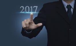 Hombre de negocios que presiona el texto 2017 sobre el fondo azul, nueva y feliz Imagen de archivo libre de regalías