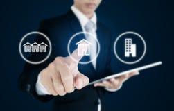 Hombre de negocios que presiona iconos de las propiedades inmobiliarias en la pantalla Inversión empresarial en propiedades inmob Imágenes de archivo libres de regalías